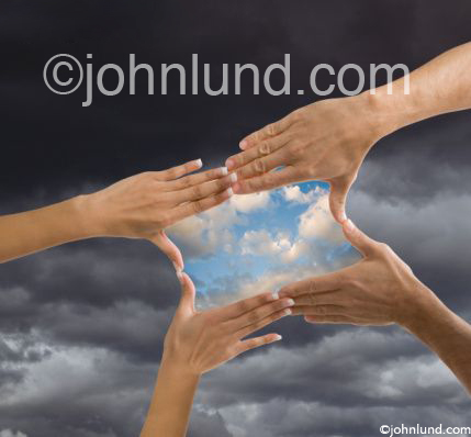 Four hands come together framing clearing skies in a storm to symbolize teamwork, optimism, vision and possibilities.