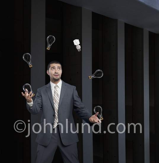 An Hispanic businessman is seen juggling light bulbs, one being a green energy bulb, illustrating the concept of