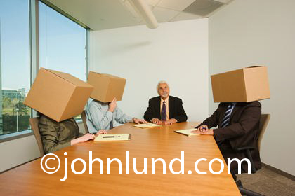 Funny picture of a group of businessmen in a meeting and wearing boxes on their heads.  Block heads in a business meeting at the conference table. Pictures of frustration.