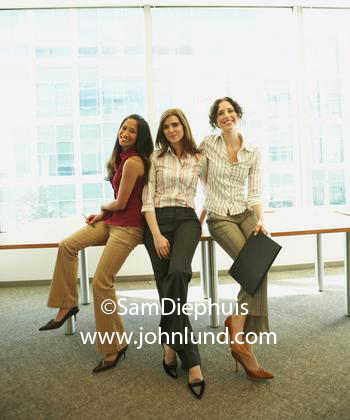 Three bright attractive young adult women sitting on the boardroom table having their picture taken. Attractive happy young businesswomen in high heels at the office. Pics of office friends.
