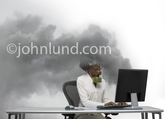An African American businesswoman wears a gas mask as she works at a computer with toxic smoke pouring from the display indicating computer problems, malware, viruses or objectionable content