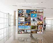 A video wall in a modern, upscale airport displays travel imagery directed towards vacation travelers.