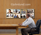 Photo of an executive sitting in front of eight video displays showing business people and meetings in an image illustrating teamwork and communications technology.