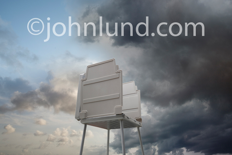 Picture of a voting machine against a sky filled withs storm clouds and the winds of change.