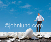 Picture of a businessman walking on eggshells in a concept stock photo dealing with issues of delicacy and judgement. A man gingerly walkig on thousands of broken egg shells litering the ground. Deep blue sky background.