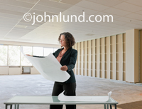 A woman architect looks at plans onsite in a new construction or commercial remodeling environment.