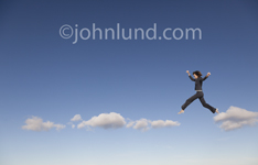 A woman leaps from cloud to cloud in this concept photo depicting cloud computing, online  networking and Internet connections.