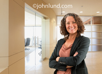 A successful businesswoman smiles warmly as she stands in an upscale office suite in this executive portrait of corporate management.