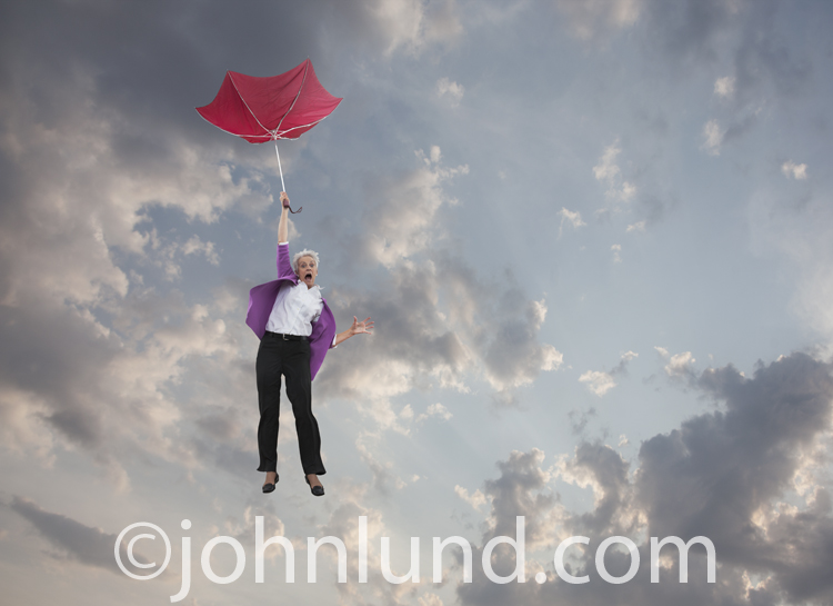 This picture of a senior woman falling through the sky holding an inverted umbrella is about losing your retirement savings and investments.