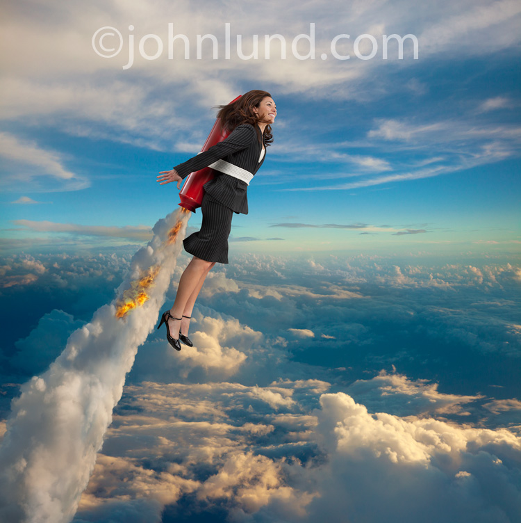 A high-flying woman soars above the clouds with a red rocket strapped to her back in a stock photo about success and achievement.