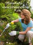 Picture of a middle-aged woman digging with a trowel in her garden. The woman is wearing gardening gloves and is planting a pretty yellow flower. A Woman Digging With a Trowel in Her Flower Garden.