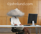 A businesswoman sits in front of a computer with her head obscured in a cloud in an image about cloud computing and lack of visibility and vision.