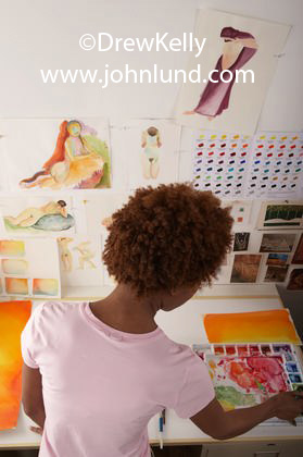 A female black artist painting in her art studio. African American woman artisit in her studio working with a painting.  Pictures of black artists.