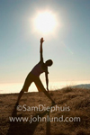 Photo of a woman stretching under a bright glaring sun. She has one arm and hand reaching for the ground and one arm and hand reaching toward the sky. Lifestyle and liesure stock photo.