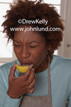 Picture of a woman eating a lemon. A cute black woman has her face a screwed up with eyes squeezed shut after a taste of a lemon wedge she is holding. Picture of a woman tasting something sour. Pics of people who eat lemons.