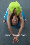 Picture of a woman laying on her back on a medicine ball. Stretching exercises with a medicine ball. Advertising picture for spas, gyms, work out plans, and active lifestyles. Picture of an African American woman using a medicine ball.