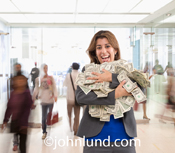 A happy, estatic even, woman smiles broadly with her arms full of dollars