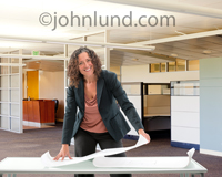 A smiling and happy businesswoman stands at a desk examining blueprints and documents in a corporate office setting.