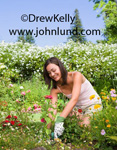 Image of a lovely young adult woman planting flowers in her garden at home. The woman has shoulder length brown hair and wearing gardening gloves and a pink blouse.  Gardening related advertising photos.