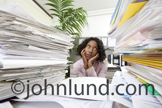 An overworked and overwhelmed African American woman sits at her desk in an office cubicle surrounded by tall stacks of paperwork and documents in a humorous look at stress in the workplace.