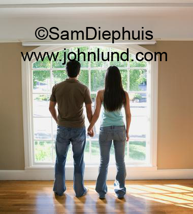 Picture of a multi-ethnic couple in their brand new home. They are standing with their backs to the camera looking out a large window in their new house. New Home owner pics.  Couple holding hands.