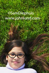 Photo of a young school girl laying on her back in thick lush grass looking up at the camera. The girl is wearing glasses and has long brown hair spread out around her head.  She is wearing a white sweater.  Only her head an shoulders are in the photo.