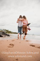 A mother and daughter walk arm-in-arm down a tropical beach, sandals in hand, sharing and intimate moment of connection.