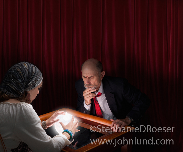 A businessman gazes intently into a fortune teller's crystal ball in this concept stock photo.