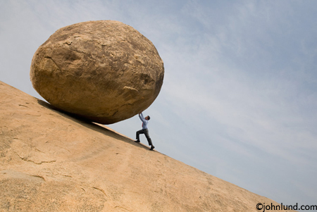 businessman pushing a boulder uphill