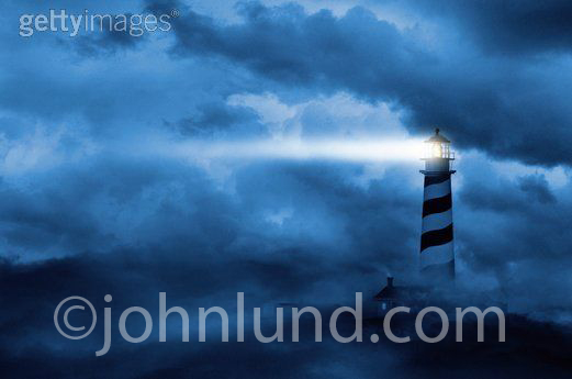 Concept stock photo of a lighthouse in the fog with beam of light shooting from lighthouse across the cloudy sky. Lighthouse emiting a powerful beacon in the night sky.