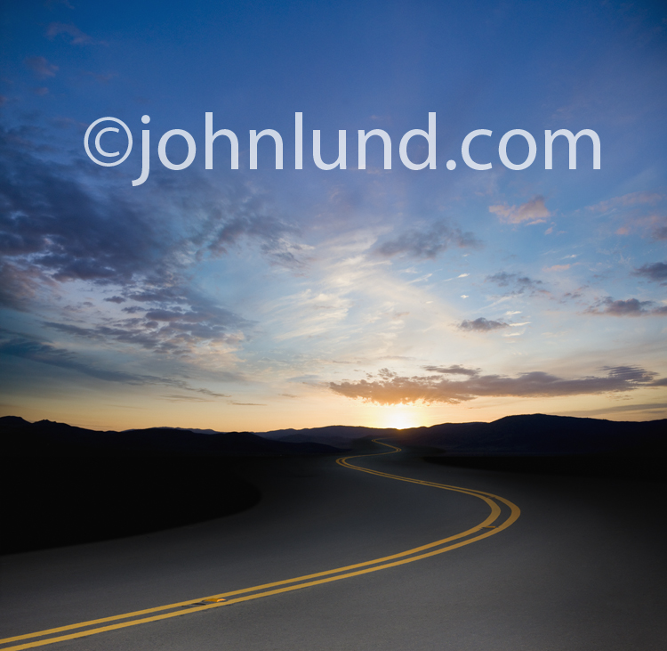 A long road winds off into a sunrise in a concept stock photo about the way forward, the future, and change.