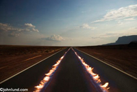 Two tracks of flames lead down a long road at dusk symbolizing the passing of something at a high rate of speed.