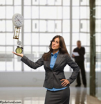 A woman executive in an office setting holds out her hand with stacked timepieces as she balances her time. The woman is balancing on her hand a couple of alarm clocks, a stop watch, an hour glass, and a wall clock.