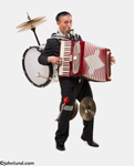 An Asian man wears the instruments of a one man band. The man has a drum, cymbals, an accordion, a harmonica, and more. Image has a plain white background.