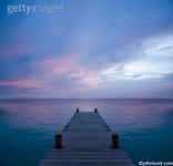 A pier juts out into the ocean at sunset in this scenic view of a tropical island called Bonaire off the coast of Venezuela.