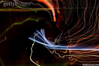 Blue, orange, green and red lights swirl in an abstract pattern of energy, motion and mystery in this concept stock photo.
