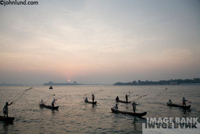 Picture of fishermen throwing nets in India. Small two man boats holding two fishermen each are fishing with nets as the sun rises on the horizon.