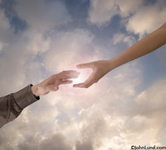 Two hands reach towards each other, the Sun Flaring as they are about to touch in a concept stock photo about connection.