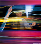 In this futuristic concept stock picture a man manages data by grabbing light streaks and seemingly controlling their flow.