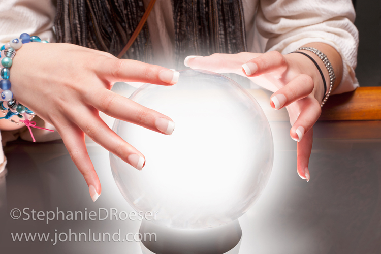 A pair of gypsy hands hover over a glowing crystal ball in anticipation of answers for the future and the way forward.