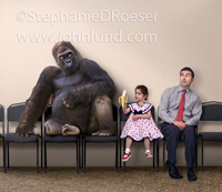 A huge Gorilla looks down suspiciously at a young girl who is offering him her banana while they sit next to each other in a waiting room.